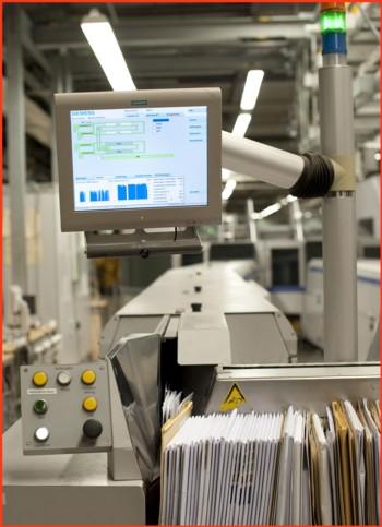Pressefoto von Siemens - die Stoffeingabe mit einem der Überwachungsbildschirme z.B. dem Durchsatz grafisch dargestellt im unteren Bereich in blau